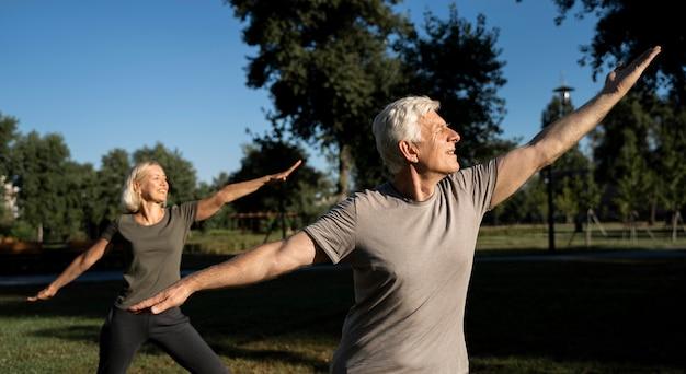 Vista lateral de la pareja de ancianos practicando yoga al aire libre