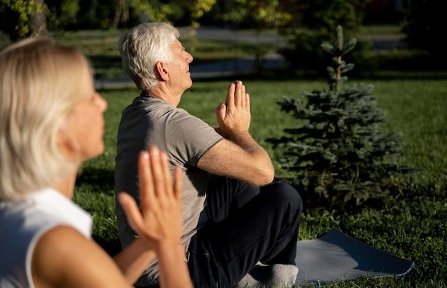 Vista lateral de la pareja de ancianos practicando yoga fuera