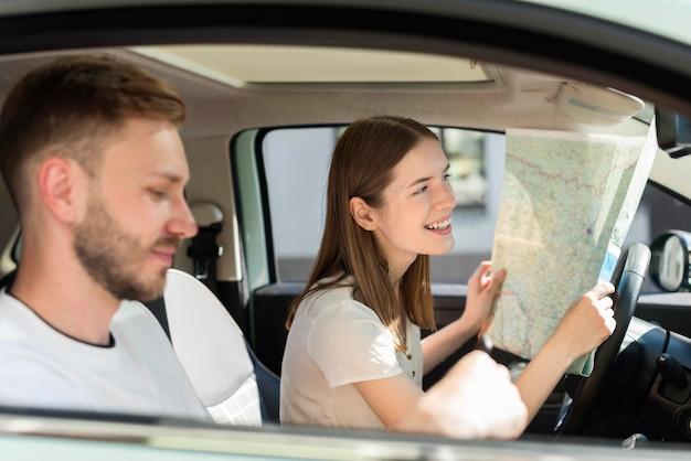 Vista lateral de la pareja en el auto mirando el mapa