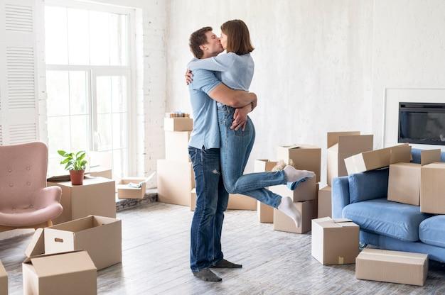 Vista lateral de la pareja besándose en casa el día de la mudanza