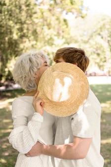 Vista lateral de la pareja besándose bajo el sombrero mientras está al aire libre