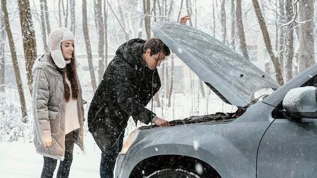 Vista lateral de la pareja comprobando el motor del coche durante un viaje por carretera