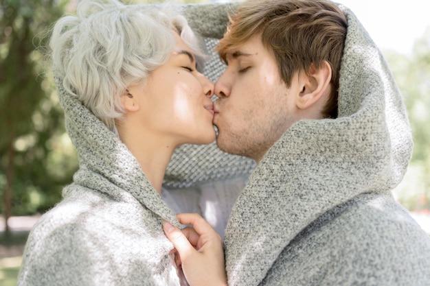 Vista lateral de la pareja cubierta de blanker besos al aire libre