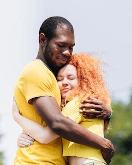 Vista lateral de la pareja interracial abrazándose