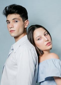 Vista lateral de la pareja posando espalda con espalda