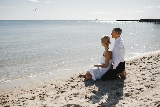 Vista lateral de la pareja que está sentada en la playa de arena cerca del mar y mirando el impresionante paisaje