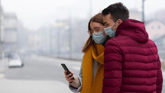Vista lateral de la pareja con smartphone en la ciudad mientras usa máscara médica