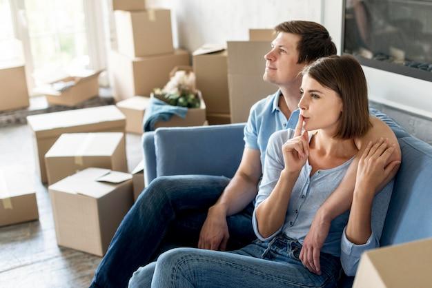 Vista lateral de la pareja en el sofá preparando las cosas para mudarse