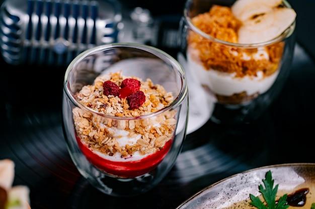 Vista lateral de parfait con yogurt muesli y frambuesa