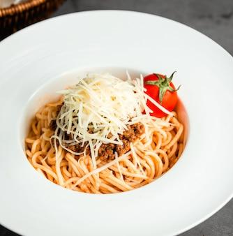Vista lateral de pasta con carne picada, queso rallado y tomate fresco en plato blanco sobre negro