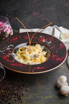 Vista lateral pasta de champiñones con champiñones y granos de pimienta negra en plato redondo