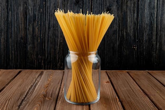 Vista lateral de pasta de espagueti en un frasco sobre fondo de madera