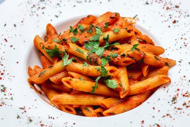 Vista lateral de pasta penne con salsa de tomate y verduras en un plato