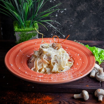 Vista lateral de pasta con salsa, parmesano, champiñones, lechuga