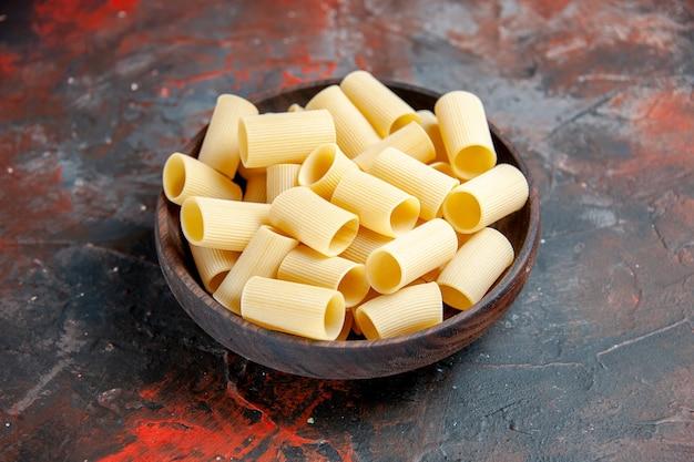 Vista lateral de pastas crudas dentro de la olla en imágenes de mesa negra
