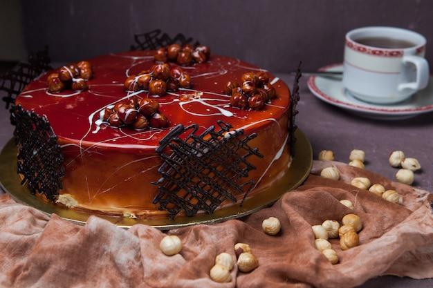 Vista lateral pastel de caramelo con nueces y taza de té en trapo