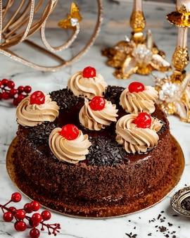 Vista lateral de pastel de chocolate con crema batida y cerezas sobre la mesa