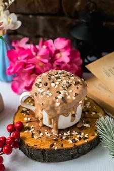 Vista lateral del pastel de chocolate con leche con chispitas de chocolate en una taza sobre una tabla de madera