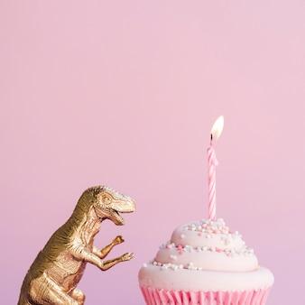 Vista lateral del pastel de cumpleaños y dinosaurio de plástico