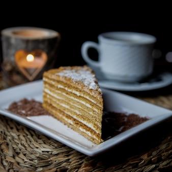 Vista lateral de pastel de miel con taza de té y velas y plato blanco en servilletas