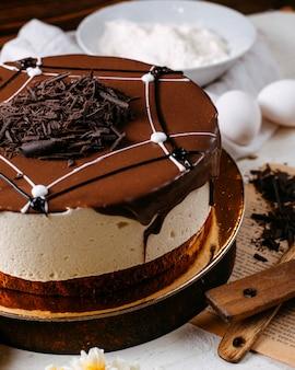Vista lateral de pastel de tiramisú cubierto con chispitas de chocolate sobre la mesa