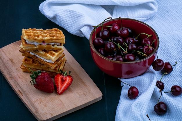 Vista lateral de pasteles y fresas en tabla de cortar con cerezas en un tazón sobre tela sobre fondo negro