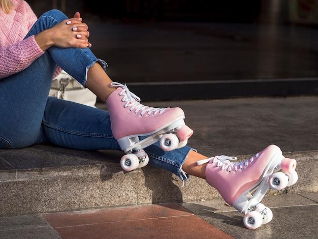 Vista lateral de patines con mujer en jeans