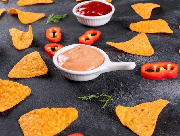 Vista lateral patrón de chips con eneldo de pimienta y salsas en tazones en piedra negra horizontal