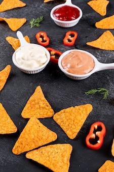 Vista lateral patrón de chips con eneldo de pimienta y salsas en tazones verticales