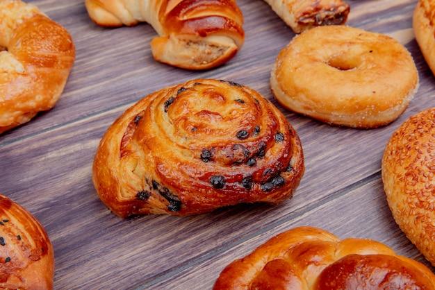 Vista lateral del patrón de diferentes productos de panadería sobre fondo de madera