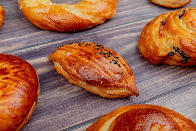 Vista lateral del patrón de diferentes productos de panadería en superficie de madera