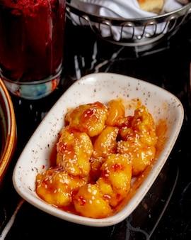 Vista lateral pechuga de pollo guisada en salsa con semillas de sésamo en un plato