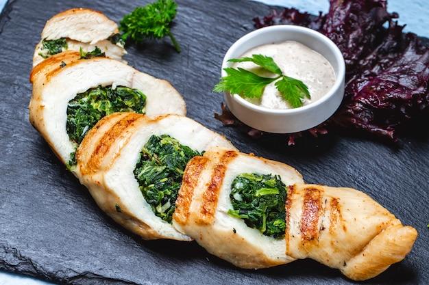 Vista lateral pechuga de pollo rellena de espinacas y salsa sobre la mesa