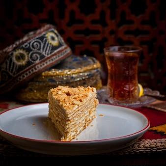 Vista lateral del pedazo de pastel con vaso de té y sombrero nacional y limón en plato blanco