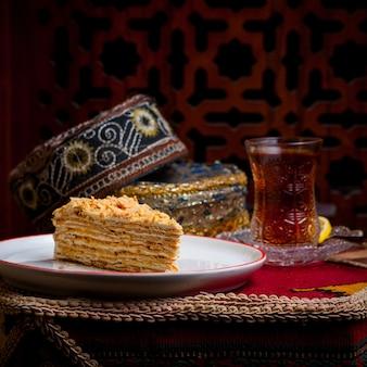 Vista lateral del pedazo de pastel con vaso de té y sombrero nacional en plato blanco