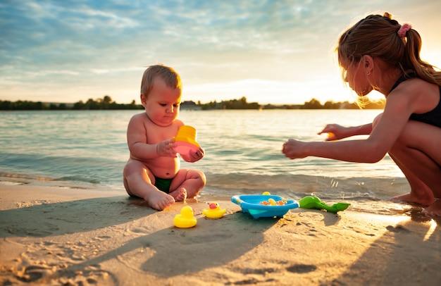 Vista lateral del pequeño bebé encantador jugando con pequeños patos amarillos de goma en la pequeña piscina azul, sentado con su hermana mayor en la arena de la playa