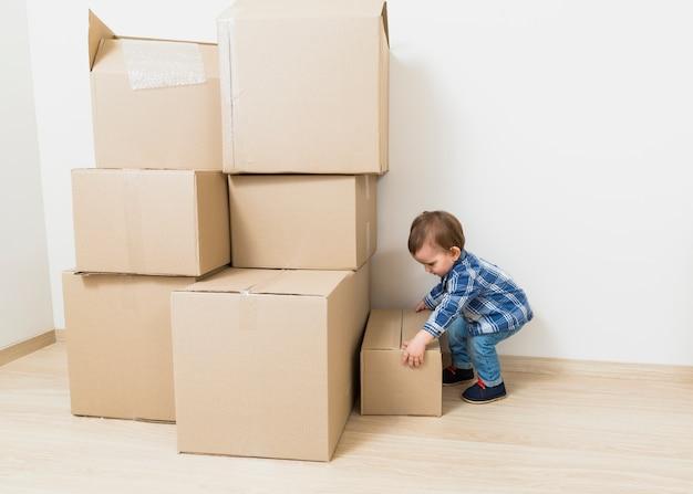 Vista lateral de un pequeño bebé que lleva las cajas de cartón del piso.