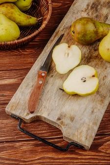 Vista lateral de peras maduras frescas y mitades en una tabla de cortar de madera con cuchillo de cocina sobre fondo rústico