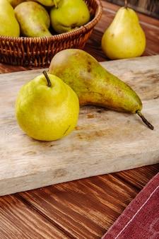 Vista lateral de peras maduras frescas sobre una tabla para cortar madera
