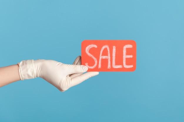 Vista lateral de perfil de cerca de la mano humana en guantes quirúrgicos blancos sosteniendo y mostrando la etiqueta de venta roja.