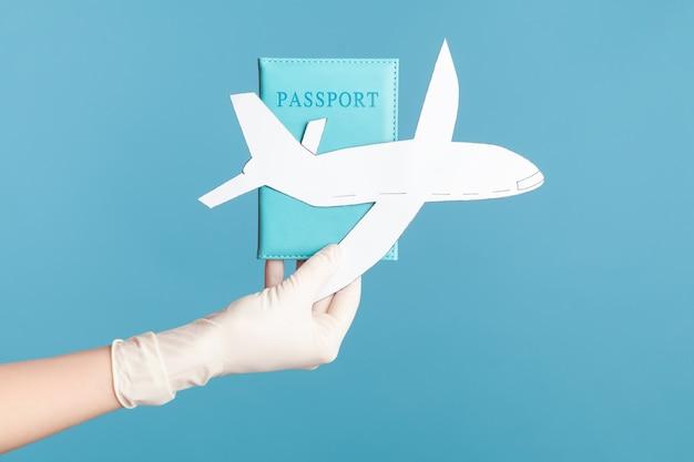 Vista lateral de perfil primer plano de la mano humana en guantes quirúrgicos blancos con pasaporte y papel de avión