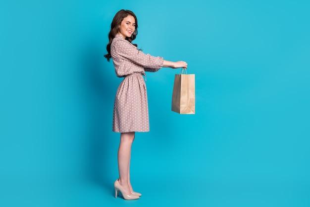 Vista lateral de perfil de tamaño de cuerpo de cuerpo entero de ella ella bonita atractiva encantadora alegre alegre alegre chica de pelo ondulado recibiendo paquete de bolsa de papel aislado fondo de color azul vibrante brillante brillante