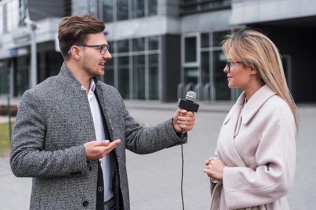 Vista lateral de periodista entrevistando