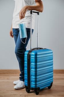 Vista lateral de la persona con equipaje y máscara médica