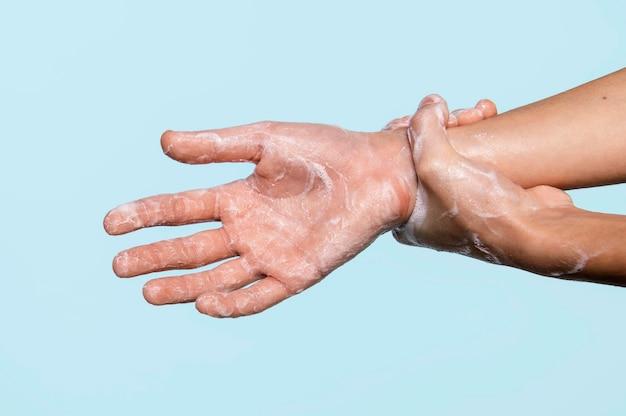 Vista lateral persona lavándose las manos aisladas en azul