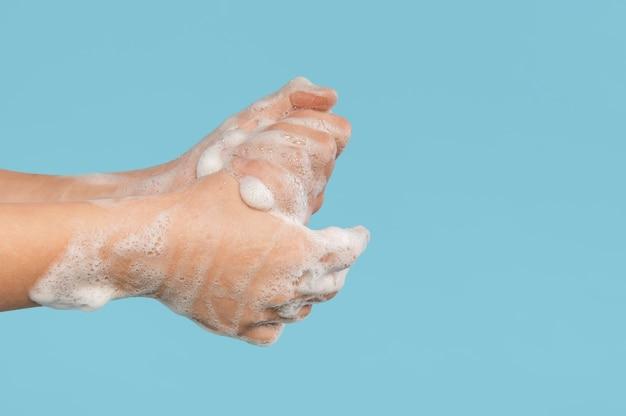 Vista lateral de la persona lavándose las manos con espacio de copia
