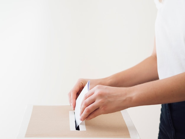 Vista lateral persona poniendo papeleta en la caja de elecciones