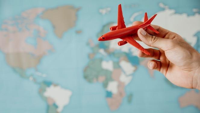 Vista lateral de la persona que sostiene una figurilla de avión sobre el mapa