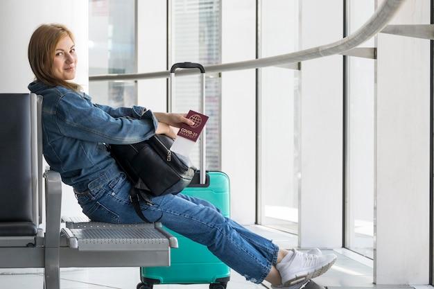 Vista lateral de la persona titular de un pasaporte sanitario en el aeropuerto.