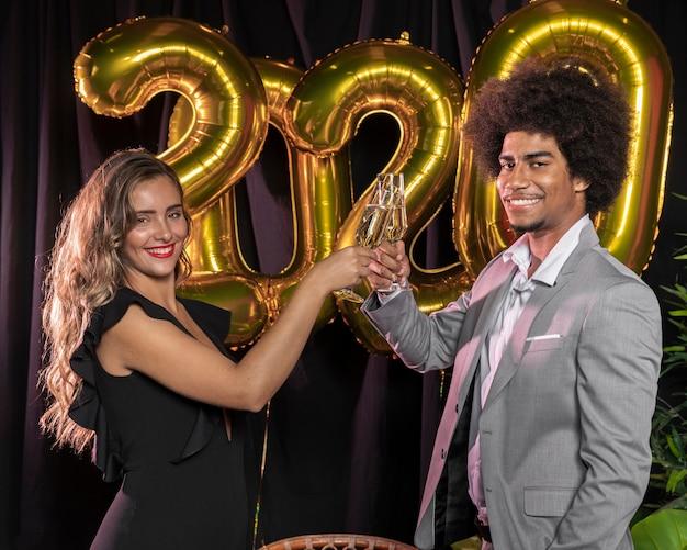 Vista lateral de personas brindando por el nuevo año 2020